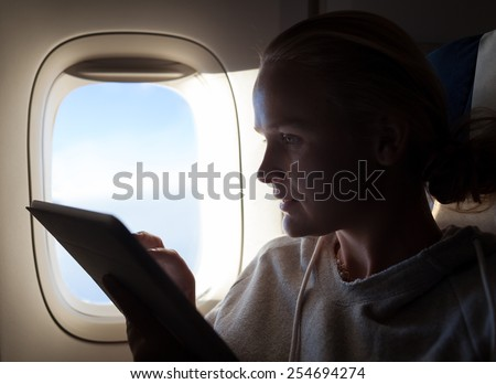 Woman typing on tablet computer sitting by illuminator in plane. Filling in time during the flight