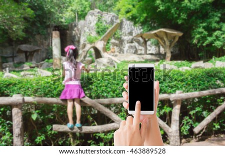 woman use mobile phone and blurred image of a child in the zoo