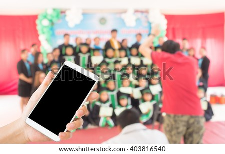 woman use mobile phone and blurred image of the cameraman take photo of children in graduation day - stock photo
