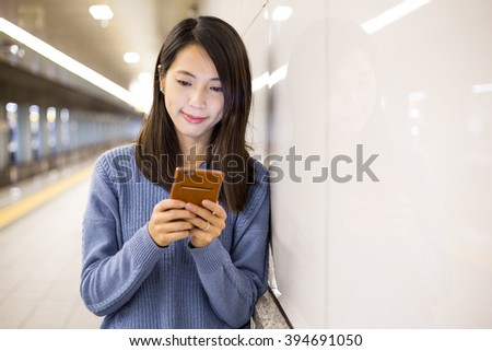 Woman use mobile phone in subway - stock photo