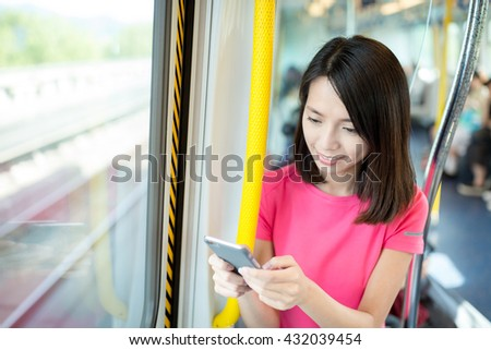 Woman use of cellphone at train compartment