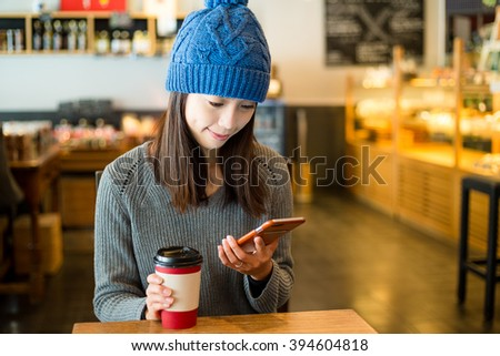 Woman use of cellphone in coffee shop at morning - stock photo