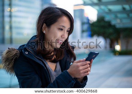 Woman use of cellphone in Hong Kong at evening