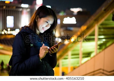 Woman use of cellphone in Tokyo city at night - stock photo