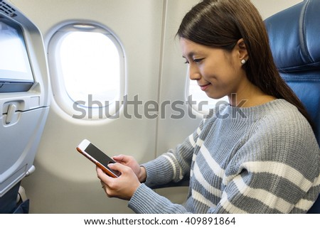 Woman use of cellphone inside aircraft