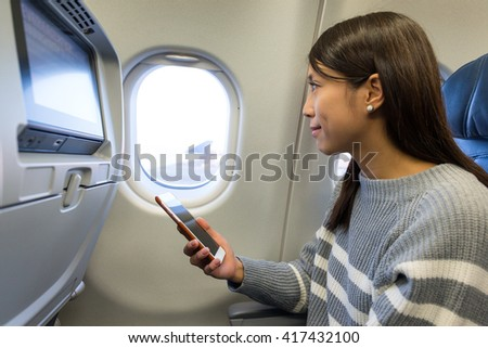 Woman use of cellphone inside airplane