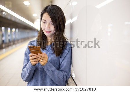 Woman use of mobile phone in underground subway station - stock photo