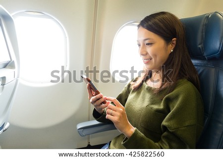 Woman use of mobile phone inside airplane - stock photo