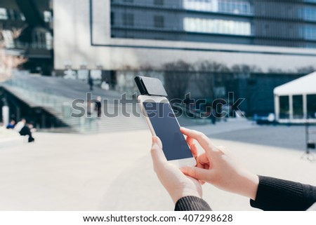Woman use of mobile phone to pay. Using Card Reader outdoors in the city - stock photo