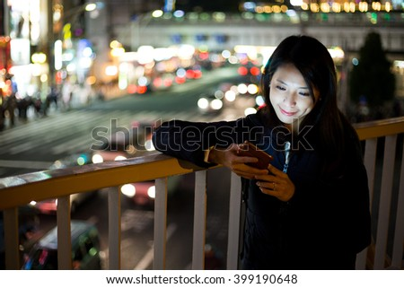 Woman use of smart phone at night in Tokyo  - stock photo