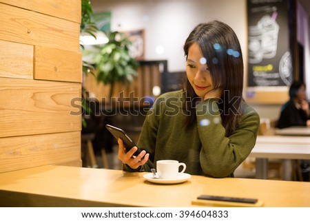 Woman use of smart phone in coffee shop