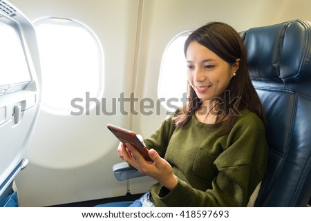 Woman use of smart phone inside airplane