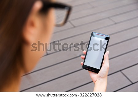 Woman use of the mobile phone with blank screen - stock photo