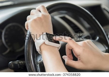 Woman use smartwatch in the car.