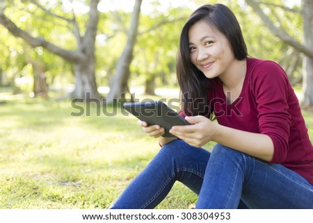 Woman Use Tablet for Relaxation at Park