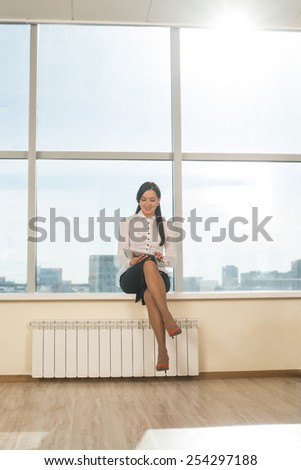 woman use tablet with sunbeam Business girl young adult sit on windowsill against blue sky window texture background Empty space for inscription Full length portrait above heating battery Sunny day - stock photo
