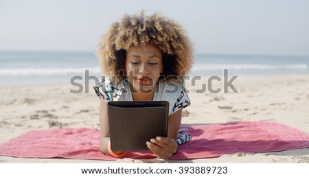 Woman Uses A Tablet On The Beach