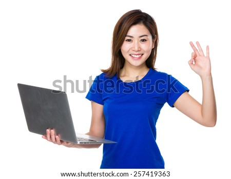Woman uses laptop and shows ok sign