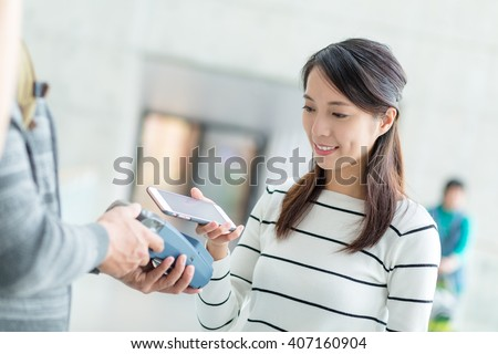 Woman usinf mobile phone to pay by NFC technology