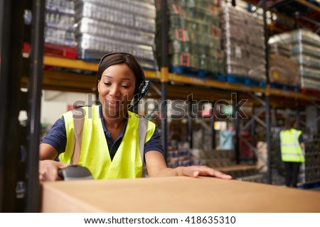 Woman using a barcode reader in a distribution warehouse - stock photo
