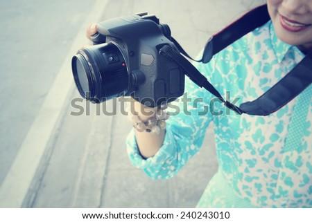 Woman using a camera to take photo - stock photo