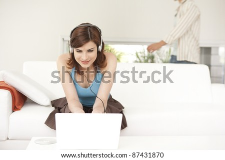 Woman using a laptop and headphones to listen to music, sitting on sofa at home.