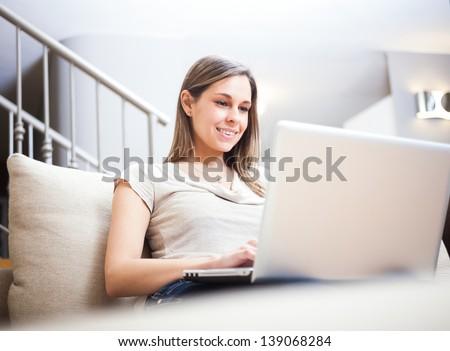 Woman using a laptop while relaxing on the couch - stock photo