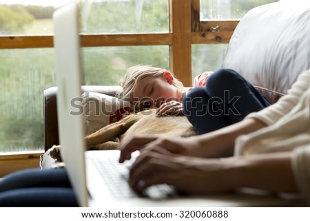 Woman using a laptop with her daughter and pet dog sleeping together next to her - stock photo