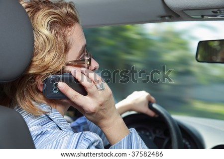 Woman using a mobile phone while she drives her car. - stock photo
