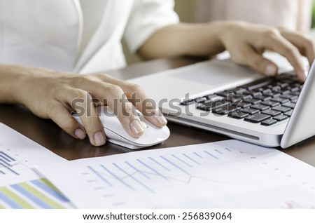 Woman using a mouse working on the computer - stock photo