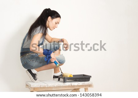 Woman using a roller to paint a wall while renovating or redecorating her house taking paint from a plastic tray
