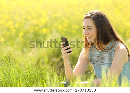 Woman using a smart phone in a green field with yellow flowers in summer - stock photo