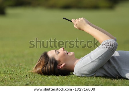 Woman using a smart phone resting on the grass in a park with an unfocused background - stock photo