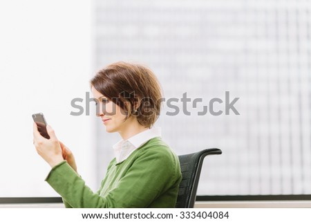 Woman using a smartphone in office by a window - stock photo