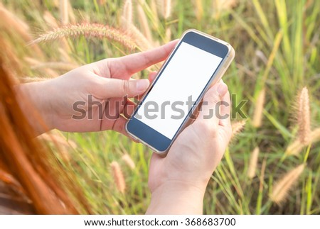 Woman Using a Smartphone on grass flowers background - stock photo