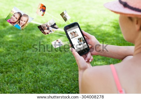 Woman using a smartphone on the grass  - stock photo