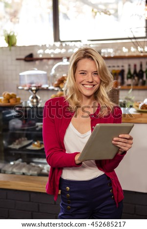 Woman using a tablet sitting and smiling in the cafe