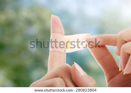 Woman using adhesive tape on finger.