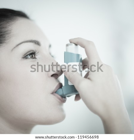 Woman using an asthma inhaler as prevention - stock photo