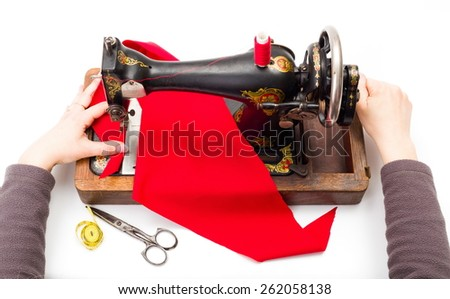 Woman using an old hand driven sewing machine - stock photo