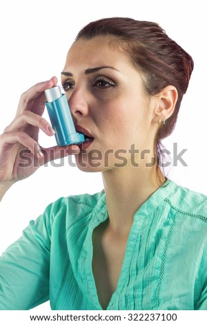Woman using asthma inhaler against white background - stock photo