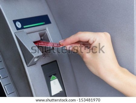 Woman using ATM  - stock photo
