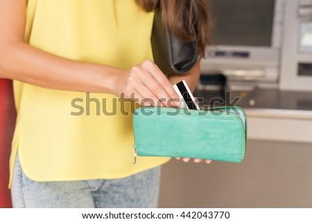 Woman using ATM card machine - stock photo