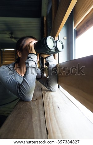 Woman using binoculars for birdwatching at wooden house