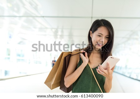 Woman using cellphone and holding shopping bag