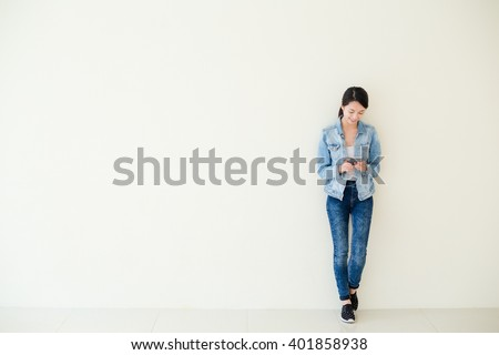 Woman using cellphone and standing against big wall  - stock photo