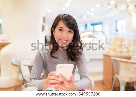 Woman using cellphone in cake shop