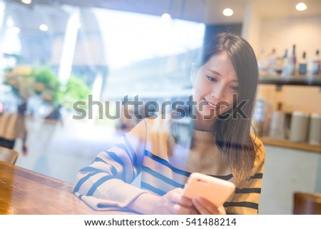 Woman using cellphone inside coffee shop