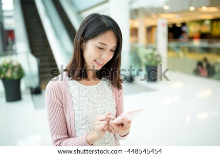 Woman using cellphone inside shopping mall