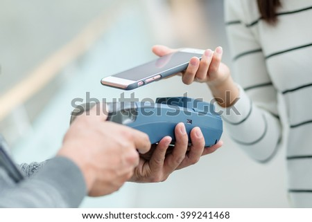 Woman using cellphone pay by NFC - stock photo